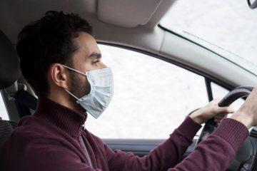 homem dirigindo usando máscara
