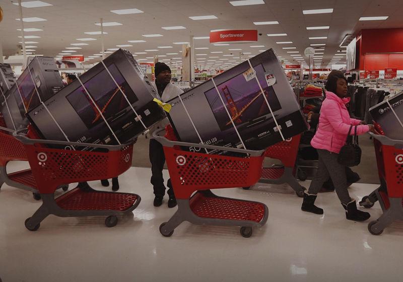 pessoas com vários carrinhos com televisores em dia de black friday