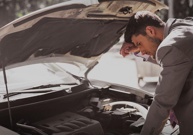 homem confuso sobre problema no carro